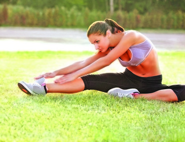 Beautiful Woman doing Stretching Exercise against Nature Backgro